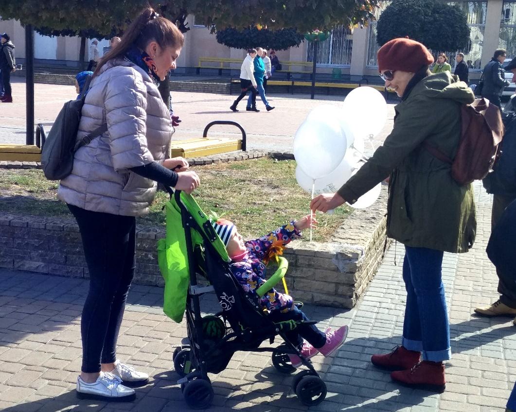 Дитина бере кульку від активістки