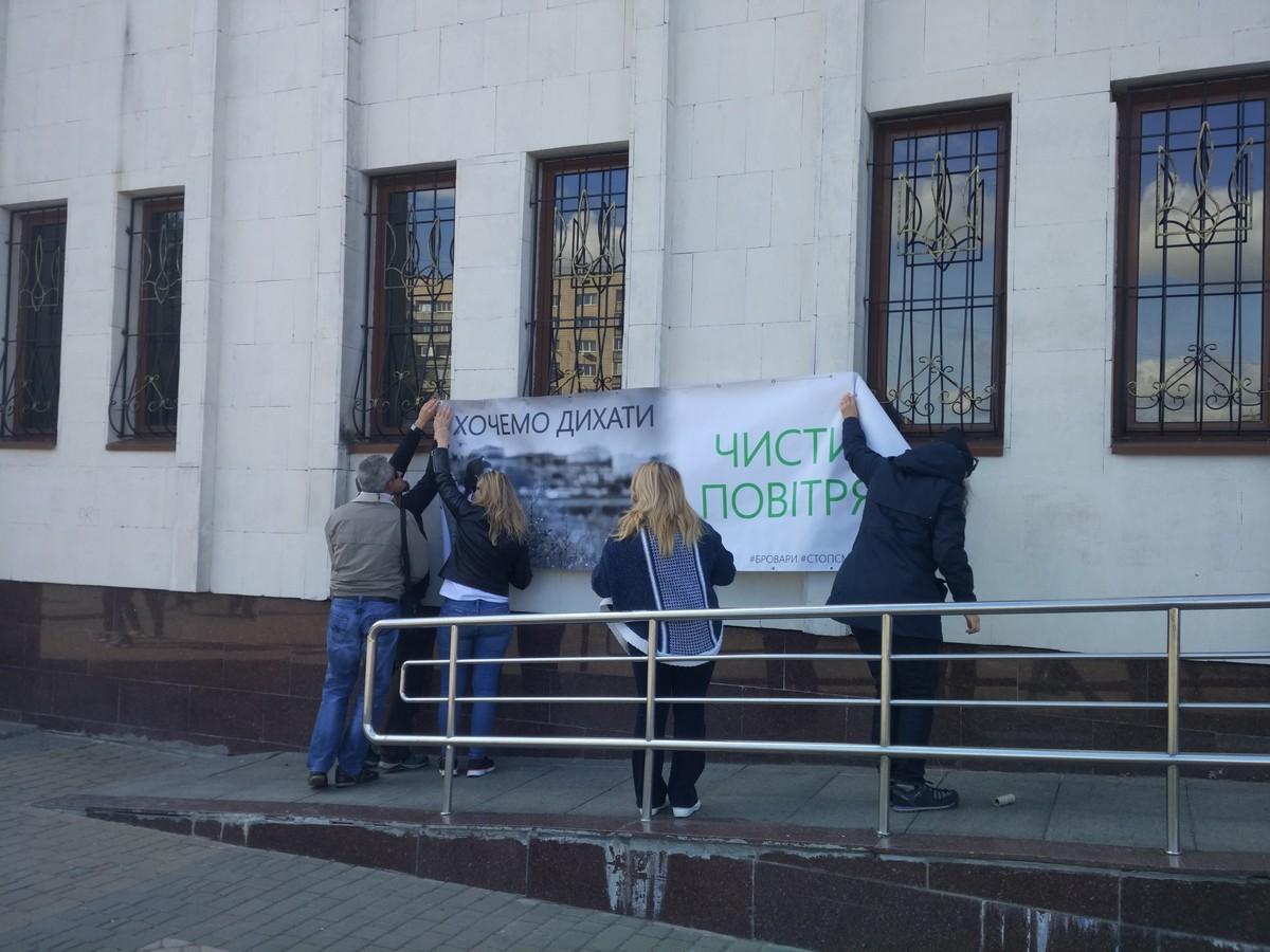 Активісти вішають банер на стіну корпусу Броварської міської ради