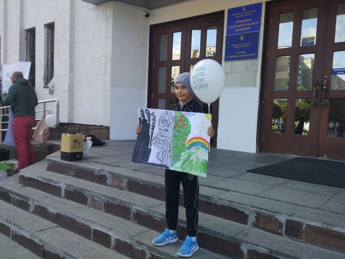 Хлопчик на екоакції із тематичними плакатом і кулькою